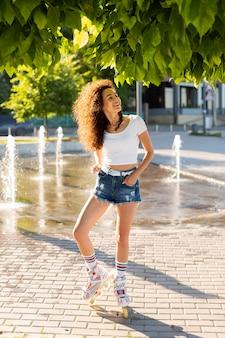 Красивая молодая женщина позирует на роликах