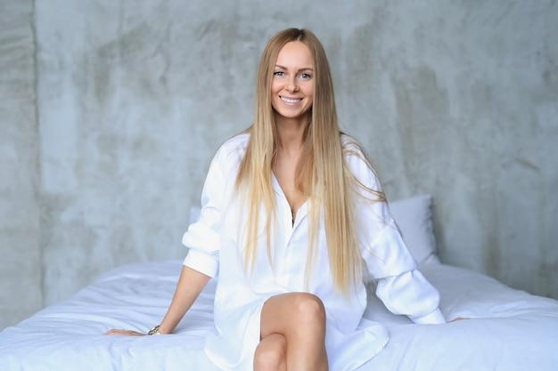 Красивая молодая женщина позирует в постели