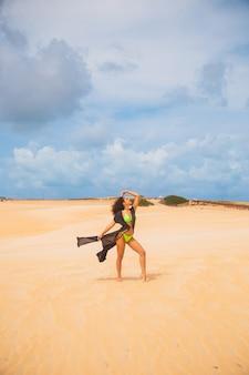 사막 모래에서 포즈를 취하는 아름 다운 젊은 여자