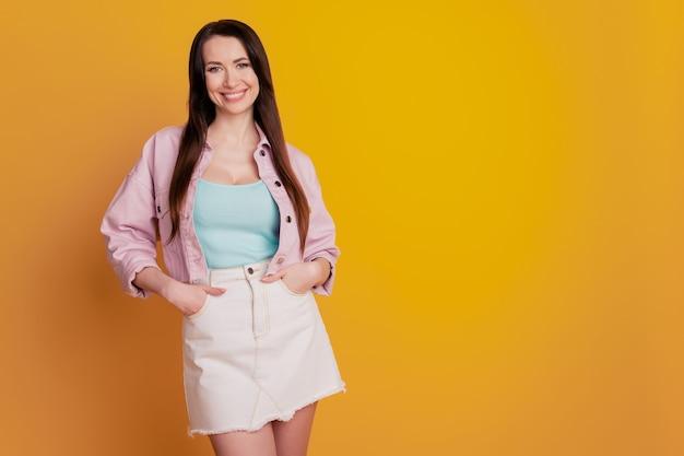 Красивая молодая женщина позирует на желтом фоне