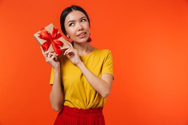 プレゼントボックスを保持しているオレンジ色の壁の上に孤立してポーズをとって美しい若い女性。