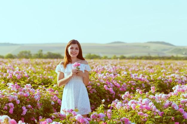Beautiful young woman posing near roses in a garden.