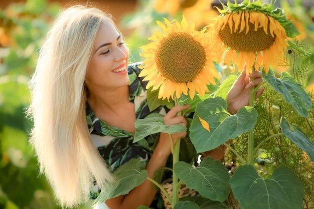 태양 꽃 근처 포즈 아름 다운 젊은 여자. 필드에서 여름 초상화입니다. 해바라기를 가진 아름다움 분야에서 행복 한 여자입니다. 태양 플레어, 태양열, 태양 광선. 곱슬 금발 여자