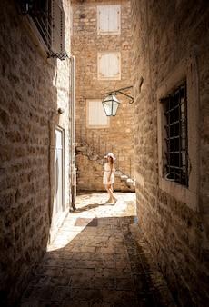晴れた日に古い狭い通りでポーズ美しい若い女性