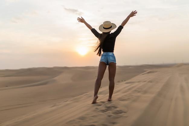 Красивая молодая женщина позирует на песке