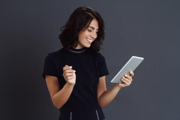 Красивая молодая женщина позирует на серую стену и держит планшет в руках