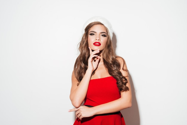 Beautiful young woman posing in red santa claus costume and hat isolated over white surface