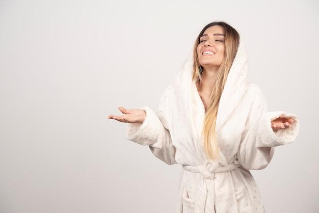 Beautiful young woman posing in a robe