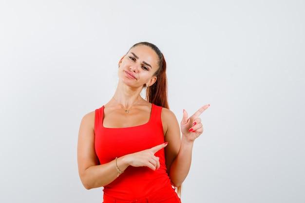 Красивая молодая женщина позирует, указывая на верхний правый угол в красной майке, штанах и выглядит уверенно, вид спереди.