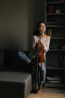 Красивая молодая женщина позирует со скрипкой дома, сидя на диване. девушка улыбается и смотрит в сторону