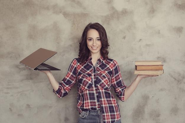 Bella giovane donna che posa con i libri e il computer portatile