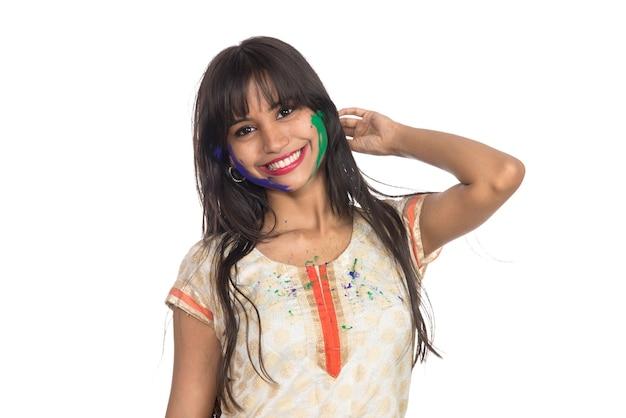 Красивая молодая женщина позирует с красочным лицом по случаю фестиваля холи на белом.