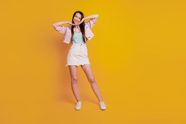 Красивая молодая женщина позирует с подбородком рук, изолированные на желтом фоне.