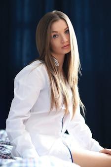 ベッドで男性のシャツでポーズをとって美しい若い女性