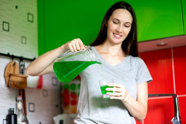 家庭の台所でガラスに青汁飲料を注ぐ美しい若い女性