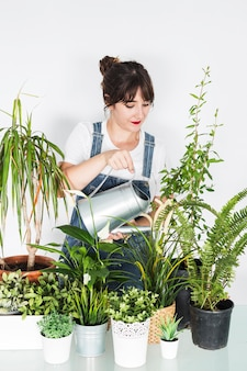 Beautiful young woman pouring water on potted plants with watering can