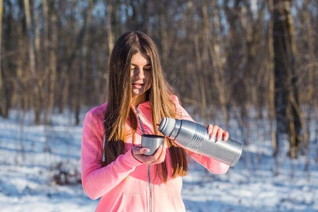 Beautiful young woman pours tea