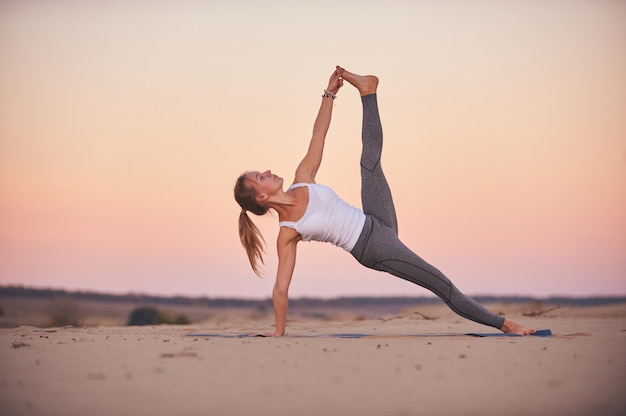 Beautiful young woman practices yoga advanced side plank pose vasisthasana in the desert at sunset