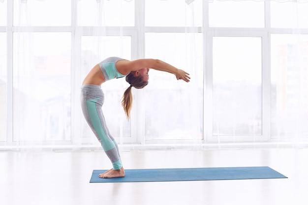 Beautiful young woman practices yoga asana ardha chakrasana - half wheel pose at the yoga class
