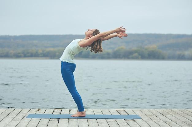 Beautiful young woman practices yoga asana ardha chakrasana