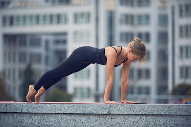 Beautiful young woman practices yoga asana chaturanga dandasana - four limbed staff pose outdoors