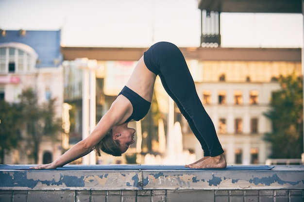 Beautiful young woman practices yoga asana downward facing dog in the city