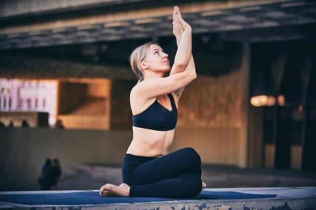 Красивая молодая женщина практикует асаны йоги гарудасана - поза орла в городе