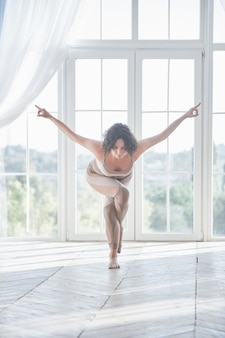 Красивая молодая женщина практикует асаны йоги гарудасана