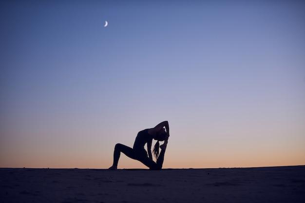 Beautiful young woman practices yoga asana king pigeon pose rajakapotasana in the desert at night