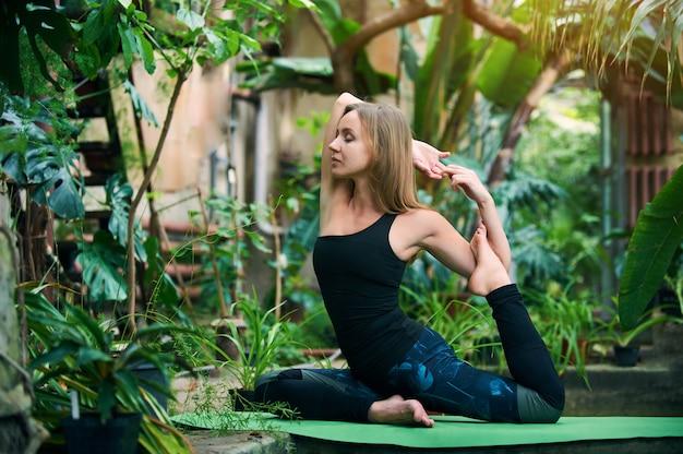 Красивая молодая женщина практикует йогу асаны король голубь позируют раджакапотасана в джунглях.