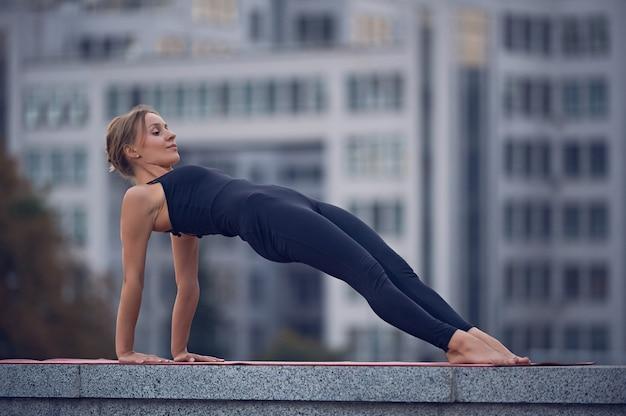 Beautiful young woman practices yoga asana purvottanasana upward plank pose outdoors