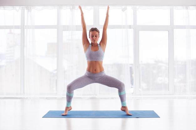 Beautiful young woman practices yoga asana stupasana at the yoga class