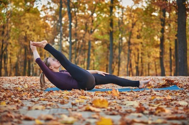 美しい若い女性は、秋の公園のウッドデッキでヨガのアーサナsupta padangushthasana 1を実践しています。