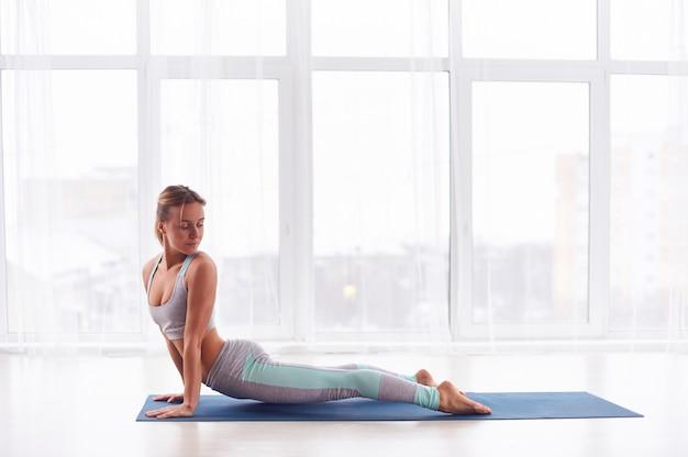 Beautiful young woman practices yoga asana urdhva mukha svanasana