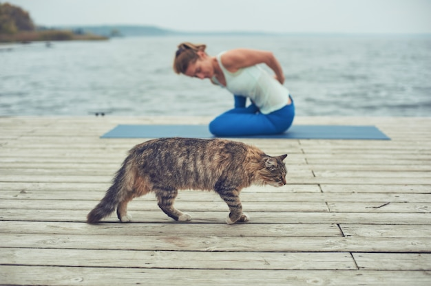 Beautiful young woman practices yoga asana on the wooden deck near the lake.