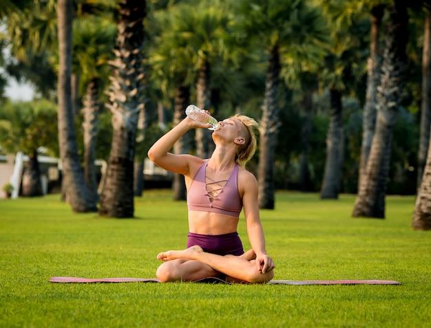 Красивая молодая женщина занимается йогой на пляже. утренняя зарядка. питьевая вода. восход