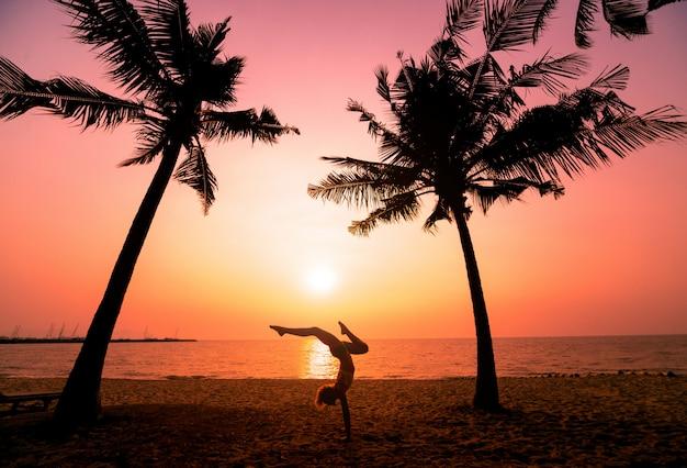 Красивая молодая женщина занимается йогой на пляже. утренняя зарядка