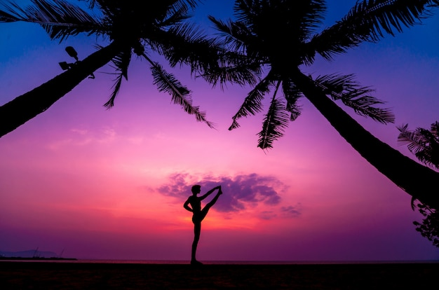 Beautiful young woman practices yoga at the beach. early morning exercise. sunrise