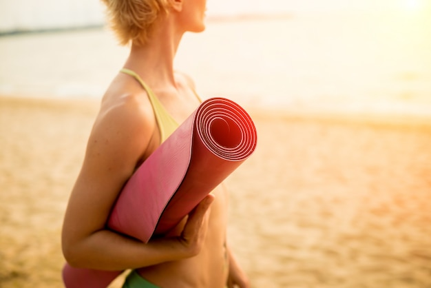 Beautiful young woman practices yoga at the beach. early morning exercise.