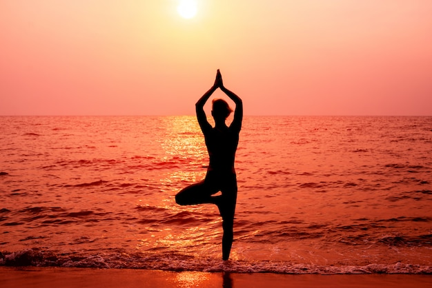 Beautiful young woman practices yoga at the beach. early morning exercise