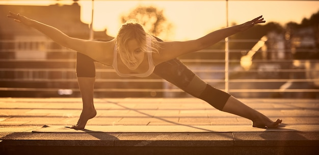 Beautiful young woman practices yoga in the terrace at sunset
