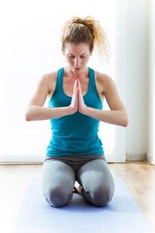 Beautiful young woman practicing yoga at home. vajrasana pose.