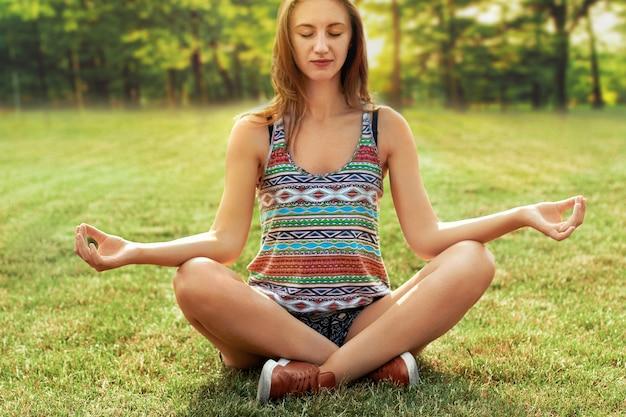 自然の中でヨガの練習の美しい若い女性。女性の幸せ。 yogahealthyとヨガの概念を行う美容女性フィットネスとスポーツ