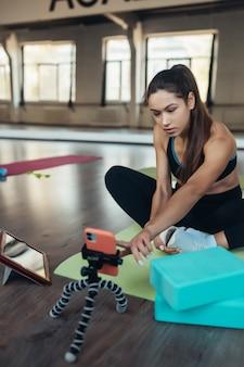 요가를 연습하는 아름다운 젊은 여성이 태블릿을 통해 온라인으로 교사와 약혼하고 있습니다. 홈 스포츠 개념입니다.