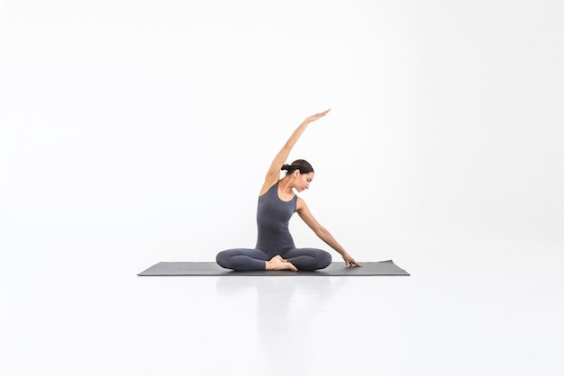 Beautiful young woman practicing yoga on the mat doing stretching