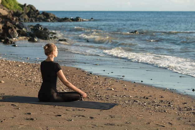 Beautiful young woman practicing yoga on sand beach