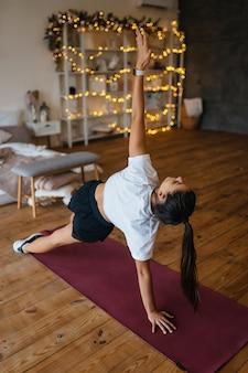 Bella giovane donna che pratica yoga a casa.