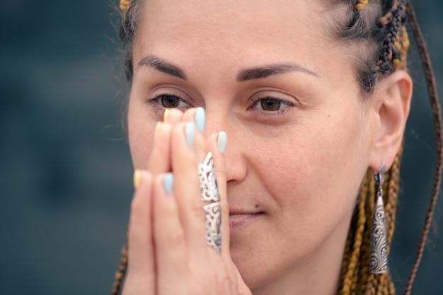 ナマステジェスチャーの肖像画のクローズアップで祈って瞑想している美しい若い女性は、精神的な彼を改善します...