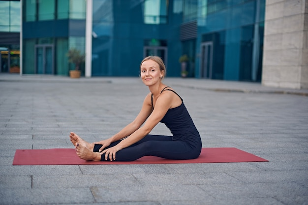 Beautiful young woman prepares to practice yoga outdoors