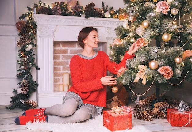 크리스마스 트리를 장식하는 새해 휴가를 준비하는 아름다운 젊은 여성